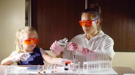 analyzes : child girl and her mother is touching a jar with chemical preparations in table in a home, examining a kit for playing Stock Footage