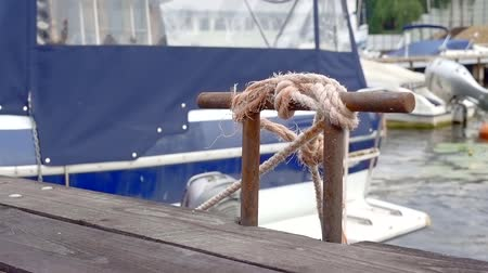 veículo aquático : boat is moored in a fishing harbor, ropes are fixing on a wooden bollard in windy weather, close-up