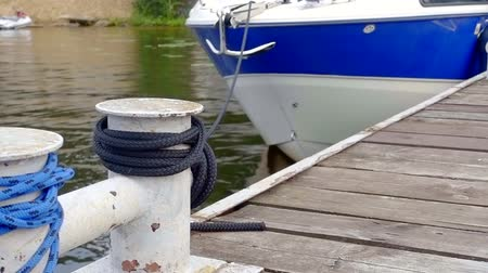 veículo aquático : view on a wooden pier and old metal knecht with fastened rope of small yacht, boat is swaying
