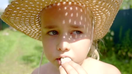 dětinský : Portrait of a beautiful little girl in hat eating a snack outside in summer.