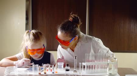 chemical agent : funny cheerful girl is watching how teacher woman is dripping chemical agent in a vial with liquid in a school class Stock Footage
