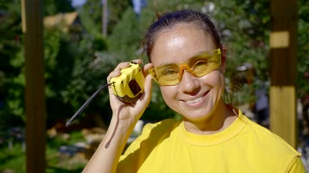 glass structure : portrait. cute woman Builder in yellow tank top and safety glasses. smiles Stock Footage