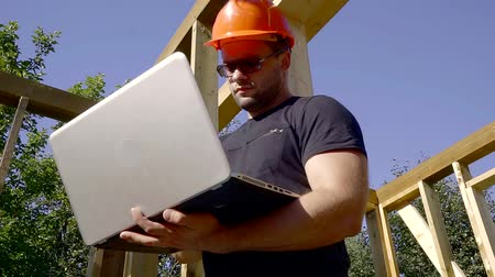 inspecting : inspector in glasses makes data in a laptop on the background of the construction of a residential house