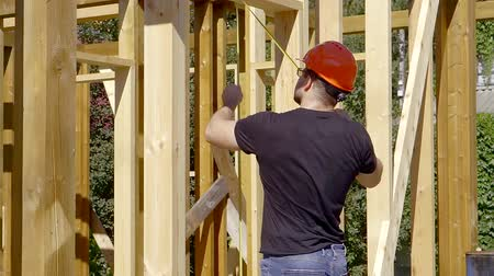 сделанный : Builder measuring doorway. the house is made of wooden beams on canadian technology Стоковые видеозаписи