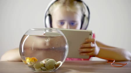 золотая рыбка : small child girl listening to music in headphones and looking at the tablet computer screen. on the table is an aquarium with gold fish