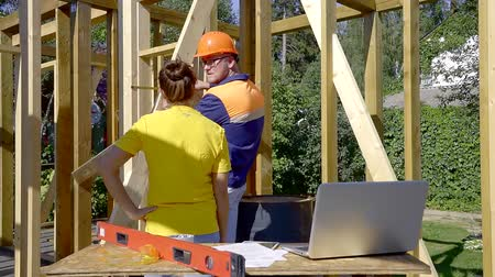 approving : Builder in a protective helmet and vest. shows the woman to the customer deviations in the construction of the drawing of the house Stock Footage