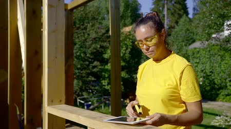 female measurements : Portrait of a female builder in yellow building glasses taking measurements on the site. Stock Footage