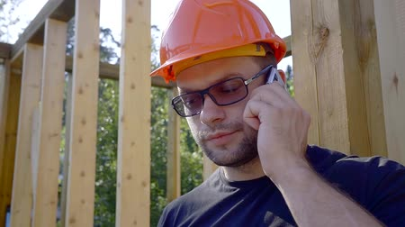 plywood : Portrait of a male builder speaking on the phone.