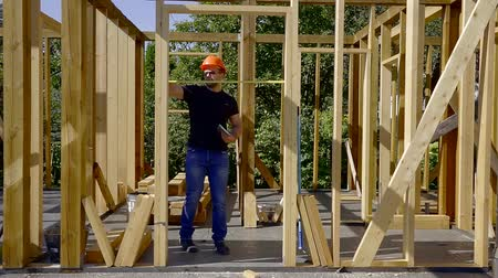 plywood : Man using measuring tape to measure distance between sides of a doorway. Stock Footage