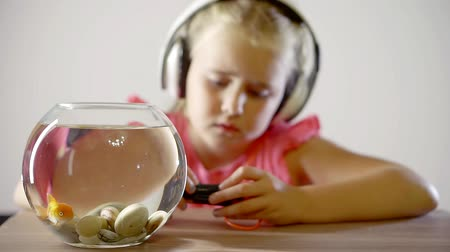 carassius : preschooler girl is sitting in room alone, hearing music through earphones, small round aquarium with red fish