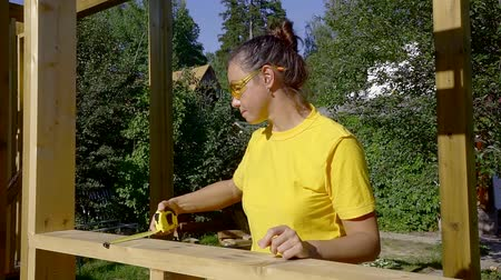 handrails : adult brunette woman is measuring a wooden handrail of house under construction in sunny day