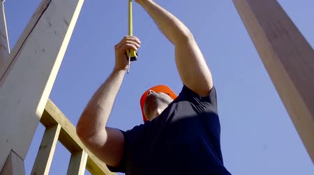 governante : tilt up view of working builder in a building site against blue sky, measuring length