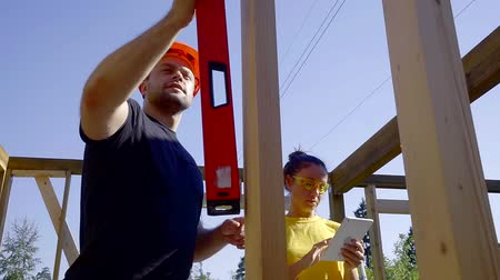 строительные леса : man and woman builders are measuring level of fixed beams in a wooden frame of house under construction