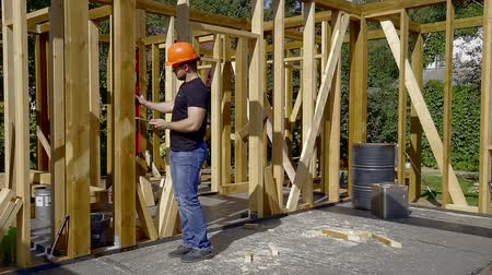 auditor : building auditor is applying a water construction level to wooden support of house frame and checking quality Stock Footage