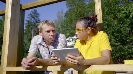 stavitel : middle aged man is explaining to brunette woman, holding tablet, standing on a construction area in villa Dostupné videozáznamy