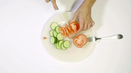 pepinos : Top view of a woman cutting vegetables for salad on a plate. Vídeos