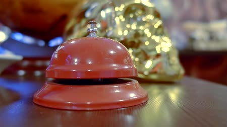 register : visitor of hotel is calling by bell for staff on reception, close-up view of hand