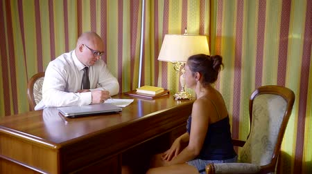everything : woman in the office of a lawyer for a consultation. a man in a shirt tie and glasses explains everything and demonstrates on paper