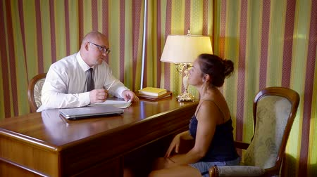договориться : woman in the office of a lawyer for a consultation. a man in a shirt tie and glasses checks documents Стоковые видеозаписи