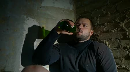 hobo : drunk alcoholic man sitting in a ruined building in the dark and drinking beer from a bottle. the degradation of personality