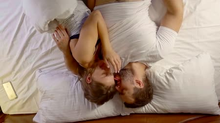прижиматься : couple lies on the evening in bed. a man amuses and plays with his woman Стоковые видеозаписи