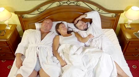 sexo : middle-aged woman woke up in her bed in the company of two partners of men and rejoices