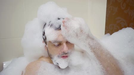 джакузи : cheerful young man playing and fooling around with soapy foam lying in the bathroom Стоковые видеозаписи
