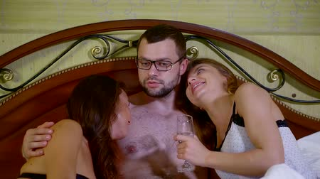 sexo : cute man with glasses in bed with two mistresses
