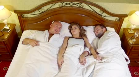 sexo : young girl wakes up in the morning in bed with two men and tries to remember what happened last night