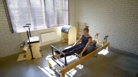 física : physical therapy of the body. Studio equipment Pilates. a girl in a black jumpsuit trains
