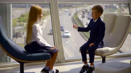 предпринимателей : Two small children at a business meeting share ideas in the office. The girl and the boy in the clothing business discuss and consider