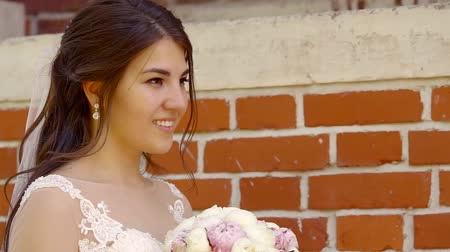 tatar : young Tatar girl bride in a wedding dress with a bouquet of cookies meets her husband standing on the street in the afternoon at the brick wall Wideo