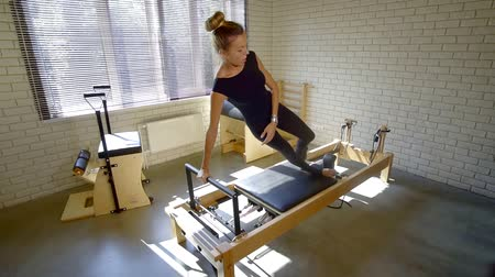 multifunctional : sports girl performs multifunctional training on the simulator Pilates. sports Studio at home