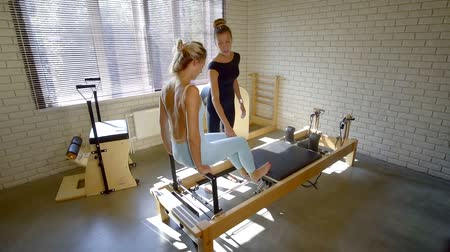 multifunctional : sports girl performs multifunctional training on the simulator Pilates. coach corrects the student in body position and movement