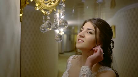 tatar : pretty Tatar bride in a wedding dress stands in the hotel corridor next to the lamp and corrects the earring in her ear Wideo