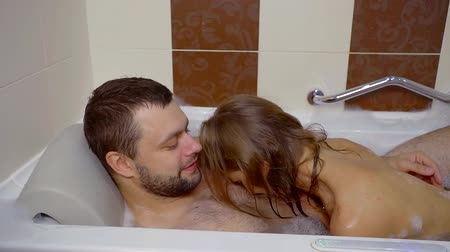 джакузи : attractive couple man and woman in bathroom with foam, enjoying the bubbling water, embracing