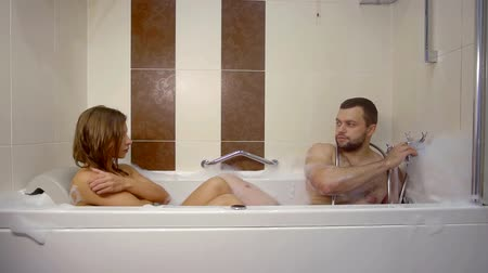 banheira : adult married couple is relaxing in jacuzzi washing in water with foam, man is adjusting faucet Stock Footage