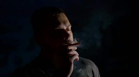 smoke kills : portrait of middle-aged bearded man, smoking cigarette and making coils from smoke in darkness