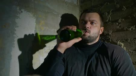 başıboş : anti-social human is drinking alcohol from bottle sitting alone in dark abandoned house