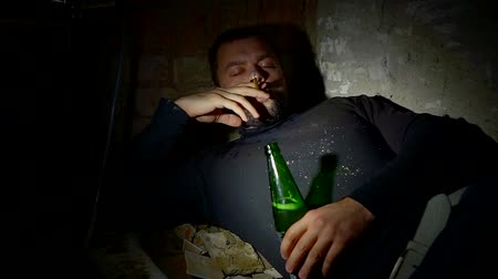 csavargó : drunken unshaven dirty bum man is lying in a darkness with cigarette and bottle with alcohol beverage