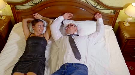 прижиматься : joyful adult loving pair is falling on bed in hotel room, man and woman are smiling and embracing