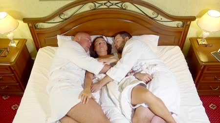 sexo : adult drunk brunette woman is waking up in bed with two men in hotel room, looking on them Vídeos