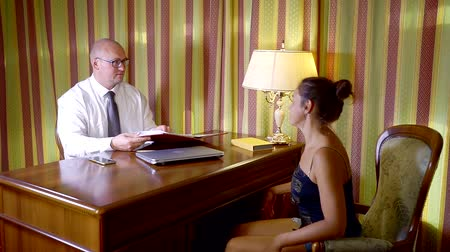 предпринимателей : middle-aged businessman is reading contract and asking questions to adult woman sitting in front
