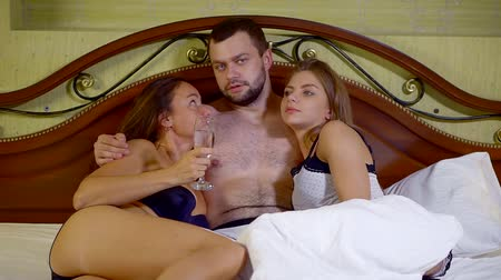 sexo : handsome man is hugging two charming naked woman lying in bed and chatting with him Vídeos