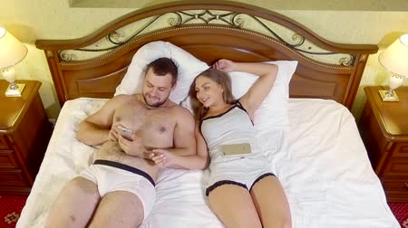 прижиматься : young family pair is lying on bed in evening with smartphones in hands, relaxing and chatting Стоковые видеозаписи