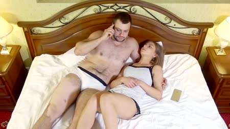 прижиматься : adult man is speaking by phone in night, lying on bed and hugging his pretty girlfriend, dissatisfied woman