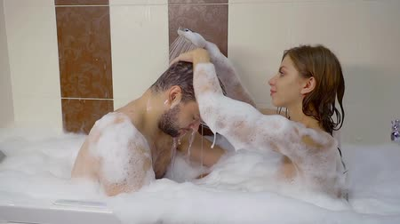 banheira : pretty woman is pouring water from shower on a head of her husband and washing his hair, sitting in bathtub together