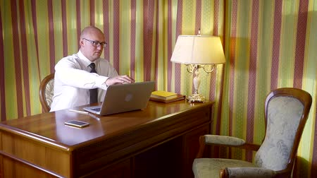 tvrdé dřevo : bald man is sitting in his office at big wooden table , opening his laptop and looking on a display