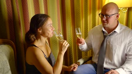 amoroso : middle-aged man and woman are drinking champagne sitting in living room in evening, smiling and talking