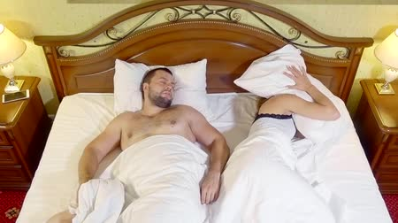 wheeze : two spouses are in a bed in evening, man is lying on back and snoring, his wife is shutting her ears by pillows
